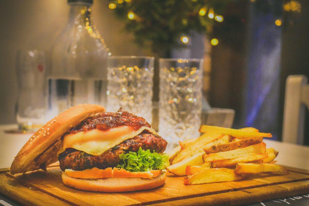 Plato poco saludable: hamburguesa con queso, salsa y pan blanco, acompañado de patatas fritas.